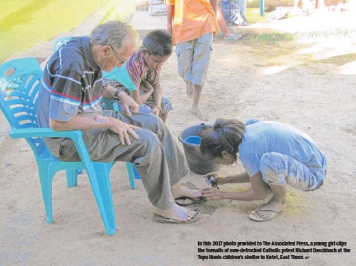 ?? AP ?? In this 2017 photo provided to The Associated Press, a young girl clips the toenails of now-defrocked Catholic priest Richard Daschbach at the Topu Honis children's shelter in Kutet, East Timor.