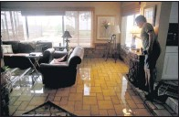 ?? THE ASSOCIATED PRESS ?? Leland Holland of Oldsmar, Fla., inspected the living room of his neighbor, Troy Shiltz, on Thursday after it was flooded overnight by Tropical Storm Eta.