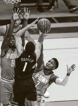 ?? Mark Mulligan / Staff photographer ?? Devin Booker of the Suns shoots over Jae'Sean Tate (8) and Victor Oladipo of the Rockets, who are using non-centers in front-court positions due to injuries.