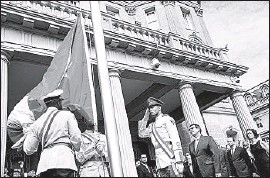 ?? Andrew Harnik Pool Photo ?? AN HONOR GUARD prepares the Cuban flag to be raised by Foreign Minister Bruno Rodriguez, center right, at the nation's embassy inWashington, D. C.
