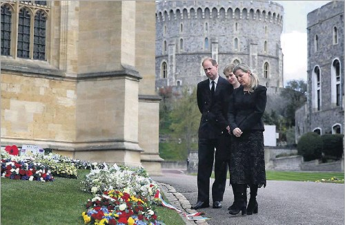 ?? Steve Parsons/agence France-presse ?? Britain's Prince Edward, Earl of Wessex, his wife Sophie, Countess of Wessex, and their daughter, Lady Louise Windsor, viewed flowers placed outside St. George's Chapel at Windsor Castle on Friday. People continued to leave flowers at the castle, 20 miles west of London, despite official entreaties to stay away because of COVID-19.