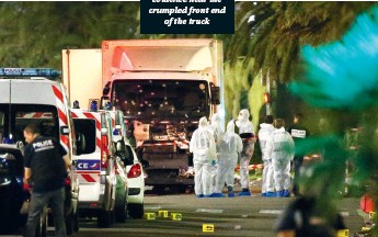 ??  ?? French police and forensic officers investigate and mark evidence near the crumpled front end of the truck