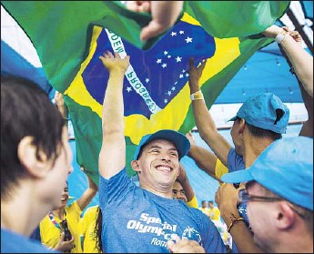 ?? Photographs by Kent Nishimura Los Angeles Times ?? UNDER THE BRAZILIAN FLAG, Florin Dinu of Romania and his Special Olympics teammates dance with athletes from Brazil on the pier in Santa Monica. The World Games are set to begin in Los Angeles.