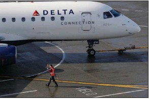 ??  ?? A ramp worker guides a Delta Air Lines plane at Seattle-Tacoma International Airport in Seattle in this file photo. Delta Air Lines lost $1.2 billion in the first quarter, but executives said Thursday that the airline could be profitable by late summer.