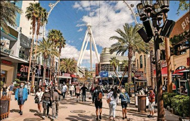 ?? CHRISTOPHER REYNOLDS | Los Angeles Times/TNS ?? With the arrival of spring and the loosening of COVID-19 restrictions, Las Vegas is welcoming more tourists. On the Strip, the Linq Hotel's Linq Promenade, with its 550-foot High Roller Ferris wheel, is a popular outdoor attraction.