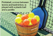 ??  ?? Pickleball, a cross between tennis and badminton, is played with a plastic ball and a paddle