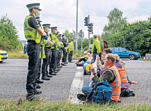 ??  ?? Police look on at protesters from Insulate Britain, a splinter group of Extinction Rebellion, who blocked roads