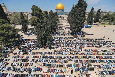 ?? Ahmad Gharabli / AFP via Getty Images ?? Muslim worshipers take part in the first Friday prayers of the fasting month of Ramadan at the AlAqsa Mosque compound in Jerusalem's Old City. Coronavirus lockdowns kept the site offlimits last year.