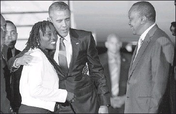 ?? Evan Vucci Associated Press ?? PRESIDENT OBAMA'S half-sister, Auma Obama, greets him at the airport as Kenyan President Uhuru Kenyatta looks on. Obama appears no longer worried that such a trip might be construed as too personal.