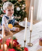 ??  ?? ABOVE AND BELOW: Pull out the candlesticks and set the table with a treasured runner or tablecloth. Add a special accent at each plate, such as sprigs of rosemary and a bell.