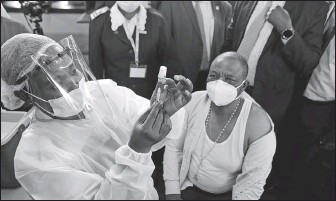 ?? TSVANGIRAY­I MUKWAZHI / ASSOCIATED PRESS ?? A nurse prepares to give a shot of Sinopharm vaccine to Zimbabwean Vice-President Constantin­o Chiwenga at hospital in Harare on Thursday. Chiwenga become the first person in Zimbabwe to receive the jab, marking the first phase of the country's vaccinatio­n campaign.