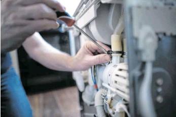 ?? FOTO: UTE GRABOWSKY/IMAGO-IMAGES ?? Ein Servicetechniker bei der Reparatur einer Spülmaschine: Viele Handwerker leiden unter der Corona-Krise. Bei der Handwerkskammer Ulm sind bereits 3500 Anträge auf Soforthilfe eingegangen.
