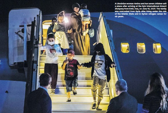 ??  ?? A Ukrainian woman Amina and her seven children exit a plane after arriving at the Kyiv International Airport Zhulyany from Erbil, Iraq, on June 16, 2021. The family was evacuated from Syria after living under the rule of the Islamic State and in Syrian refugee camps for six years.