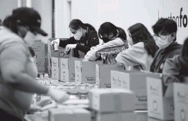 ?? JUSTIN SUL­LI­VAN Getty Im­ages ?? Vol­un­teers pack emer­gency dis­tri­bu­tion boxes at the Hous­ton Food Bank on Satur­day to be given out to res­i­dents in need af­ter win­ter storm Uri swept across 26 states with a mix of freez­ing tem­per­a­tures and pre­cip­i­ta­tion last week.
