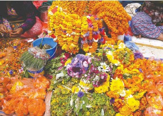 ?? VIOLET ST. CLAIR ?? Tangerine-coloured marigolds are offered for sale at a stand on the streets of Kathmandu.