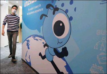 ?? (AP file photo) ?? An employee walks past a graphic of the Ant Group's mascot at the company's office in Hong Kong. Ant Group has tangled with Chinese regulators for years as its operations have grown.