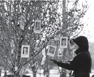 ??  ?? Carol Schaefer, from Southwest Harbor, Maine, looks at one of the many photos of service members hanging from trees during the groundbreaking and remembrance ceremony for the Colorado Fallen Heroes Memorial on Monday in Denver.