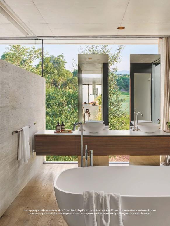 ??  ?? Los espejos y la bañera exenta son de la firma Inbani, y la grifería de la bañera es de Vola. El blanco de los sanitarios, los tonos dorados de la madera y el revestimiento de las paredes crean un conjunto cromático armonioso que dialoga con el verde del entorno.