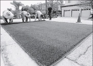 ?? Luis Sinco Los Angeles Times ?? A CREW from Smartgrass Synthetic Turf rolls out a pre-measured piece of artificial grass for installation in the backyard of a home in Pacific Palisades. Water officials aren't sure if turf reimbursements will be taxable.