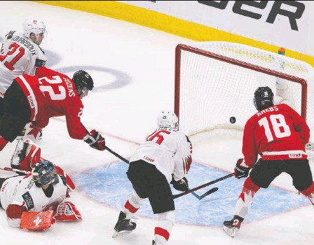 ?? GREG SOUTHAM ?? Canada's Dylan Cozens shovels the puck past Switzerland goalie Noah Patenaude during second-period action at the world juniors Tuesday in Edmonton. Team Canada scored four times in the second period to break open a close contest and remain unbeaten through three starts.