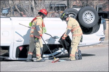 ?? PHOTOS BY MAX LEVY / Loveland Reporter-herald ?? Loveland firefighters scoop broken glass off of the roadway after a crash that flipped a Chevy Silverado pickup truck and damaged at least one other vehicle next to Blue Ribbon Auto Body on Sunday.