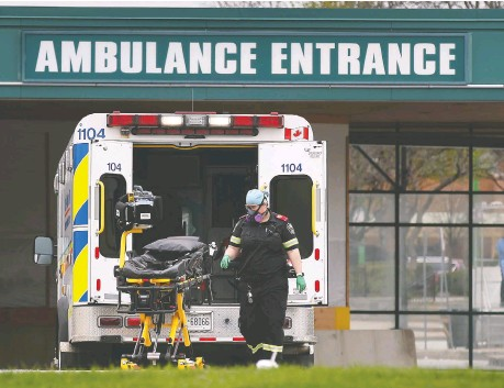 ?? DAN JANISSE ?? A paramedic loads a stretcher on Friday at the Windsor Regional Hospital Met Campus. Windsor is transporting stable COVID-19 patients from Toronto to be cared for locally, although it is not disclosing which Toronto hospitals the patients are from.