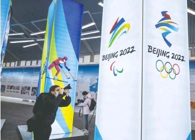 ?? KEVIN FRAYER / GETTY IMAGES ?? A journalist last week takes pictures of a display at the exhibition centre for the Beijing 2022 Winter Olympics.