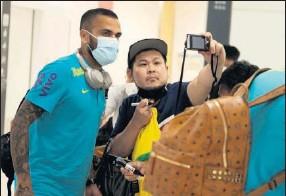 ??  ?? Dani Alves posa con un aficionado japonés en la llegada de Brasil.