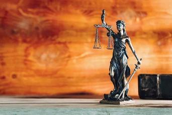??  ?? La statua bendata della Giustizia con i simboli della bilancia e della spada (iStockphoto )
