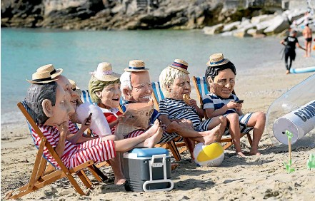 ?? AP ?? Climate activists from Oxfam wear giant heads depicting the leaders of the G7 as they participate in an action on Swanpool Beach in Falmouth, Cornwall.