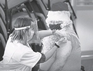 ?? ERNST PETERS/ USA TODAY NETWORK ?? Florida Presbyterian Homes CEO Joe Xanthopoulos, dressed as Santa, receives a Pfizer COVID- 19 vaccination from Walgreens pharmacist Ericka Gutierrez at the Florida Presbyterian Homes in Lakeland, Fla. in December.