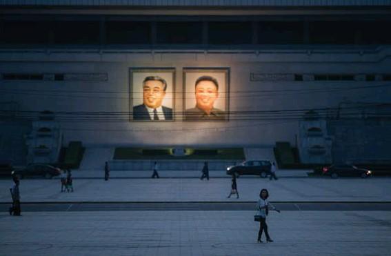 ?? © Ed Jones/afp ?? De portretten van wijlen Kim Ilsung en Kim Jongil in het straatbeeld in Pyongyang.