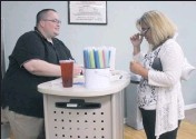 ?? CECIL WHIG PHOTO BY JANE BELLMYER ?? Mike Nelson, a coach at Queen Street Nutrition in Rising Sun, helps JoAnn Bedsworth decide which Herbalife drink she wants from a large list of choices.
