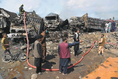?? Wakil Kohsar / AFP / Getty Images ?? Firefighte­rs and owners of fuel tankers examine debris after a huge blaze consumed trucks on the outskirts of Kabul. There was no immediate indication of whether the fire was an accident or sabotage.