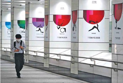 ??  ?? A man wearing a protective face mask walks next to wall decorations promoting the Olympics in Tokyo yesterday.