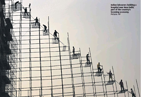 ?? Picture: AP ?? Indian labourers building a hospital near New Delhi, part of the country's booming economy.