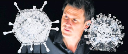 ?? Finnbarr Webster ?? > Bristol artist Luke Jerram with his glass sculpture of the Oxford-AstraZeneca coronavirus vaccine, left, alongside his earlier work of the virus itself, in glass. The sculpture, one million times larger than the actual vaccine nanoparticle, marks the ten millionth vaccination to be administered in the UK and will be sold for charity