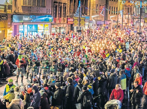 ??  ?? SEA­SONAL SPIRIT: Crowds gather in In­ver­ness as a torch­lit pa­rade takes place for the of­fi­cial switch-on of the city's Christ­mas lights