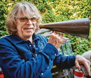 ?? Foto: Bernd Thissen, dpa ?? Musiker und Komiker: Helge Schneider mit Megafon auf der Terrasse seiner Wohnung.