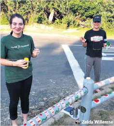 ??  ?? Elize Boshoff and Chandre Minaar busy painting the roadside poles on the road leading to Alkantstrand Zelda Willemse