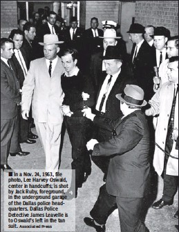??  ?? In a Nov. 24, 1963, file photo, Lee Harvey Oswald, center in handcuffs, is shot by Jack Ruby, foreground, in the undergroun­d garage of the Dallas police headquarte­rs. Dallas Police Detective James Leavelle is to Oswald's left in the tan suit.