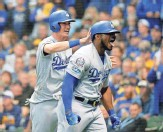 ?? JON DURR/USA TODAY SPORTS ?? The Dodgers' Yasiel Puig (right) celebrates with Cody Bellinger (left) after hitting a three-run home run against the Brewers in Game 7 of the NLCS on Saturday night.
