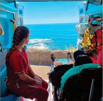 ??  ?? In spiaggia L'anziano sulla barella e accanto la volontaria davanti al mare nella foto diffusa dalla Croce Rossa