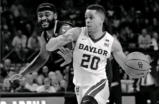 ?? Tony Gutierrez/The Associated Press ?? Baylor's Manu Lecomte drives past Tommy Hamilton IV during the second half. The Bears overcame a 3-of-14 shooting night from Lecomte.