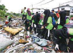 ??  ?? Volunteers clear rubbish at Kampung Sungai Kayu Ara.