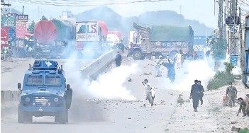 ?? — AFP photo ?? Tehreek-e-Labbaik Pakistan (TLP) party throw stones over the police armoured vehicle during a protest in Barakahu neighbourhood of Islamabad.