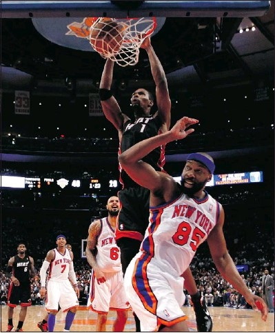 ?? — GETTY IMAGES ?? New dad Chris Bosh of the Miami Heat dunks against Baron Davis of the New York Knicks in Game 3 of the Eastern Conference quarterfinals at Madison Square Garden on Thursday.