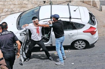 ??  ?? PALESTINIANS scuffle with a wounded Orthodox Jewish man who crashed his car near the Lions' Gate, as clashes continued at the Temple Mount in the old city of Jerusalem, yesterday. | EPA
