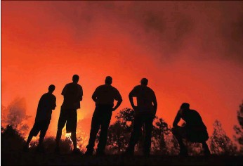 ?? PICTURE: AP ?? Residents watch as a fire burns near their homes off Morgan Valley Road in Lower Lake, California yesterday. More evacuation orders have been issued as the fire grows in northern California, threatenin­g the lake community of about 1 300 that was...