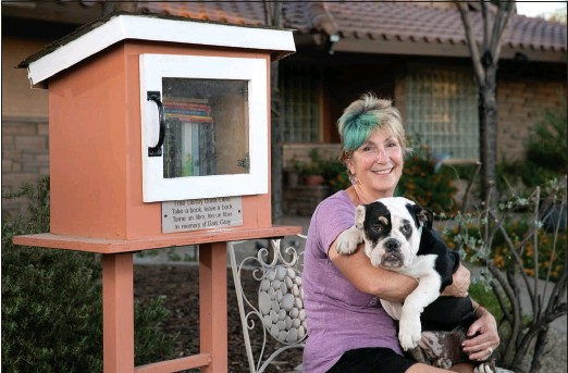 ?? STEVE MARCUS ?? Former Clark County Commissioner Chris Giunchigliani poses with her dog, Gracie, by a mini free library in front of her home.